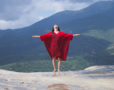 Still screen from Ascent of Weavers featuring women dressed in red on a mountain