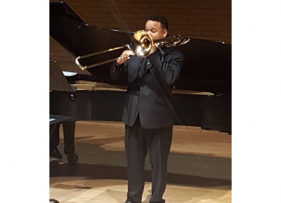 Eston Bell performing on stage with his trombone