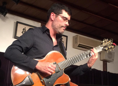 Davy Mooney performs on guitar in a club environment