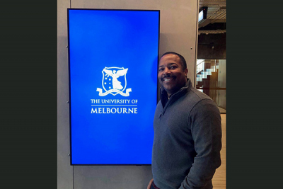 Nick Williams posing in front of University of Melbourne sign